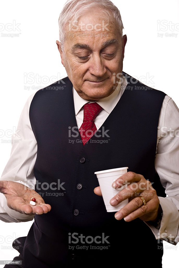 Senior man taking a pill royalty-free stock photo