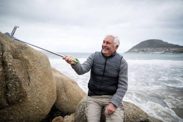 ältere mann unter ein selbstporträt von selfie stick - senior bilder wasser stock-fotos und bilder