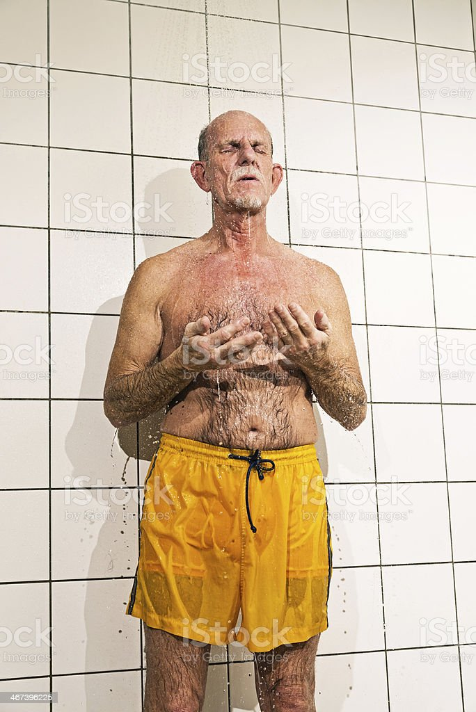 Senior man taking a shower in bathroom. stock photo
