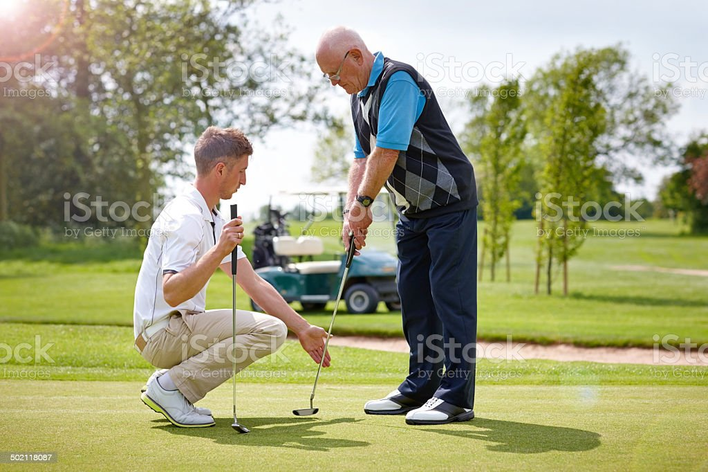 Senior man taking golf lessons from club pro stock photo