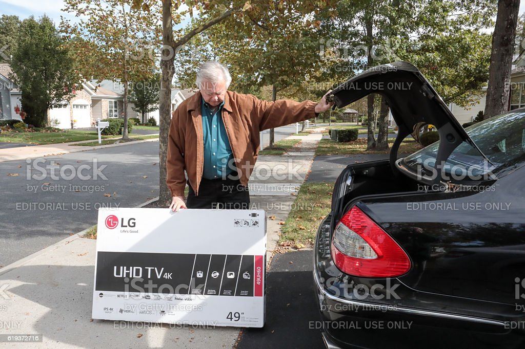 Senior man taking new television out of car trunk stock photo
