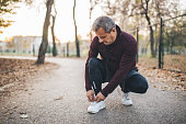 Senior man taking pause from jogging to tie his shoelace