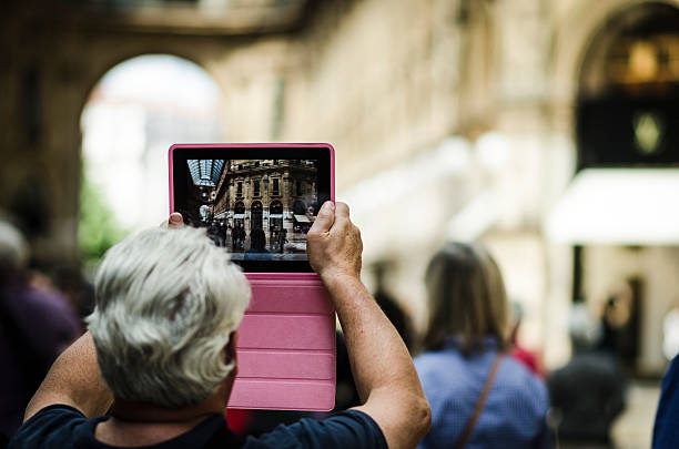 Senior man taking photograph with a digital tablet in Milano foto