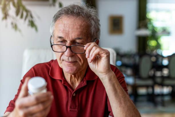 Senior man taking prescription medicine at home stock photo