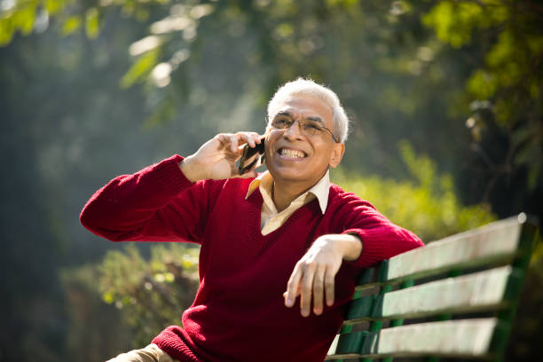 Senior man talking on mobile phone at park stock photo