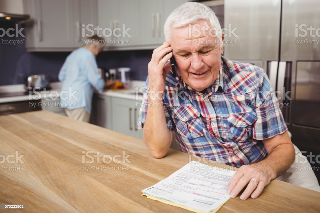 Senior man talking on phone and woman working in kitchen royalty-free stock photo