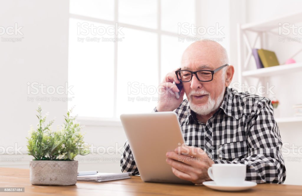 Senior man talking on phone with tablet stock photo