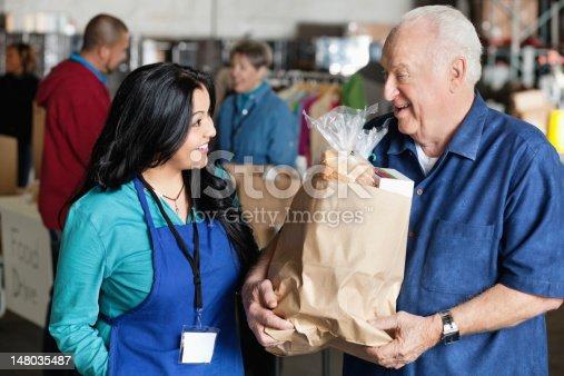 istock Senior man talking to food donation volunteer 148035487