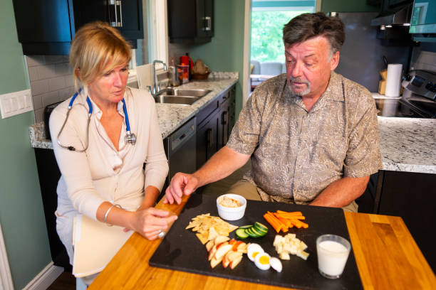 A senior man talking with a visiting nutritionist at home stock photo