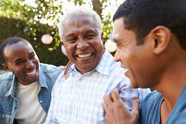 senior man talking with his adult sons in garden, - three people stock photos and pictures