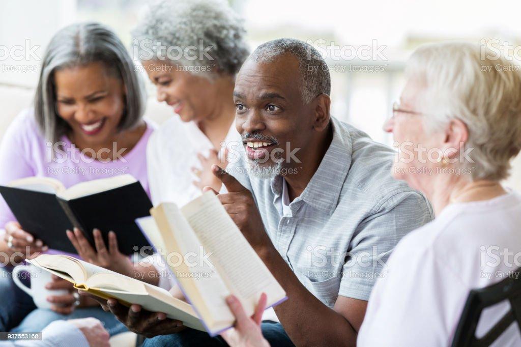 Senior man tells joke during outdoor book club meeting stock photo
