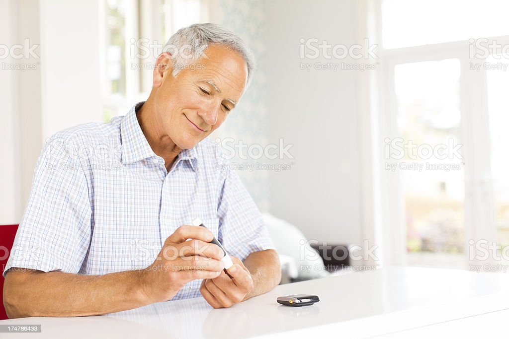 Senior Man Testing His Blood Sugar Level With Glucometer. stock photo