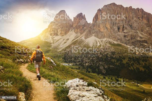Senior man trail hiking on high mountain: by the Sella pass, with Saslong on background