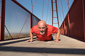 Senior man training and stretching on bridge in outdoors image