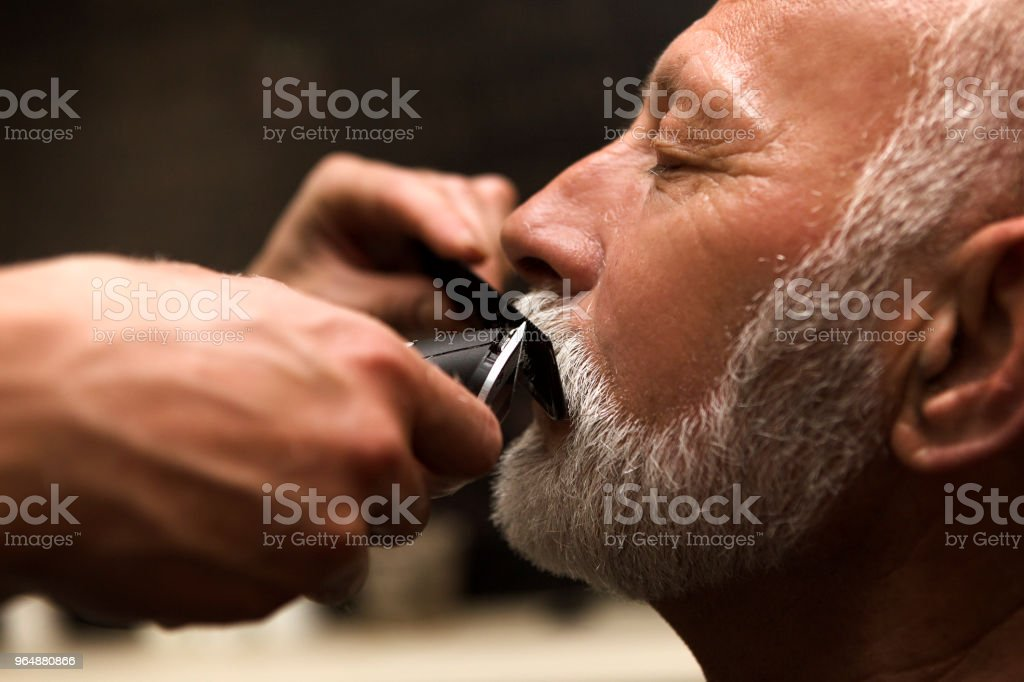 Senior man trimming mustaches at barber royalty-free stock photo