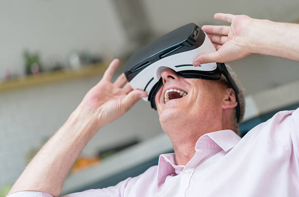 Senior man trying a VR device - Photo
