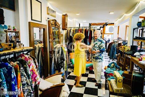 Hispanic senior woman helping husband button up colorful Hawaiian shirt during weekend shopping trip in Buenos Aires.