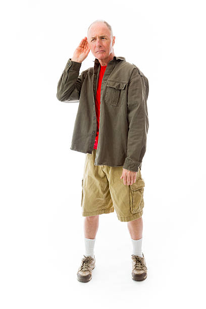 Senior man trying to listen isolated on white background stock photo