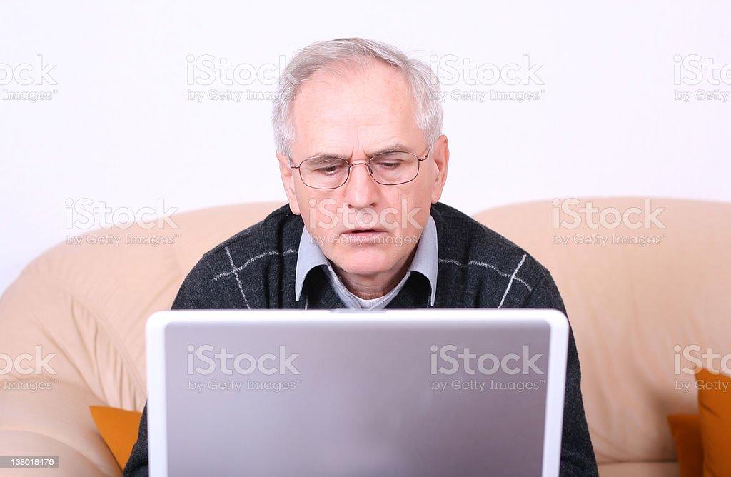 Senior man typing on a laptop royalty-free stock photo