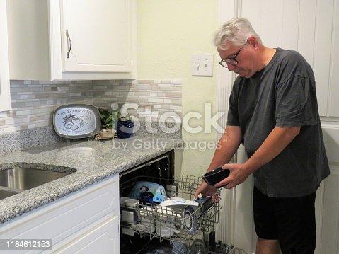 istock senior man unloading dishwasher 1184612153