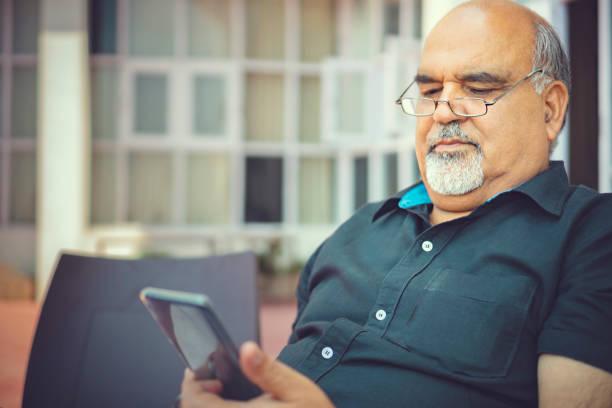 Senior man uses a smartphone. stock photo