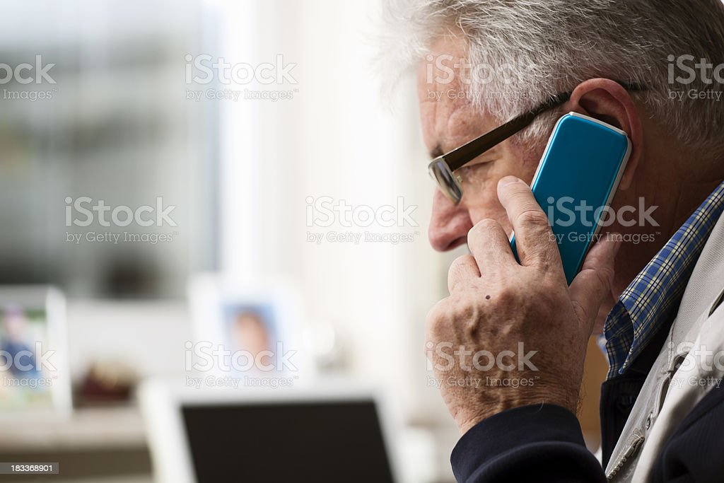 Senior Man Using a Cellphone at the Office royalty-free stock photo