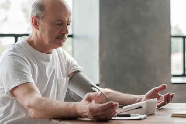 Senior man using a home blood pressure machine to check his vital statistics