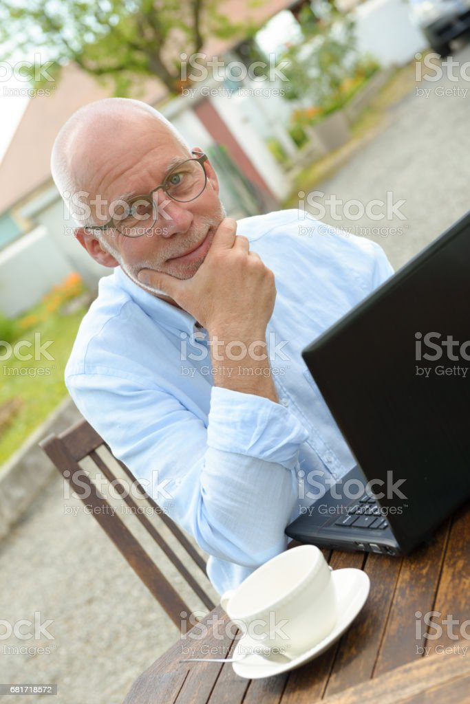 senior man using a laptop outside stock photo