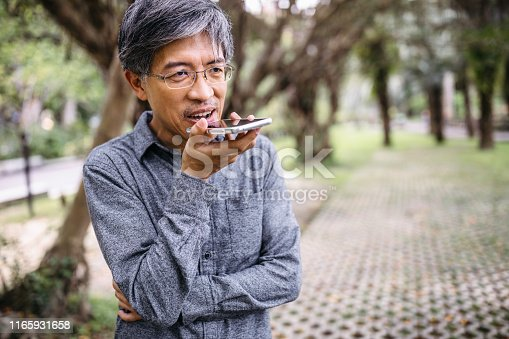Senior Asian man using smartphone, recording audio message in the park