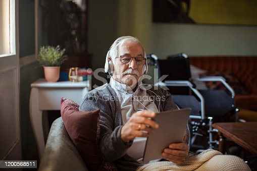 Close up of a senior man using his tablet on the couch with his dog