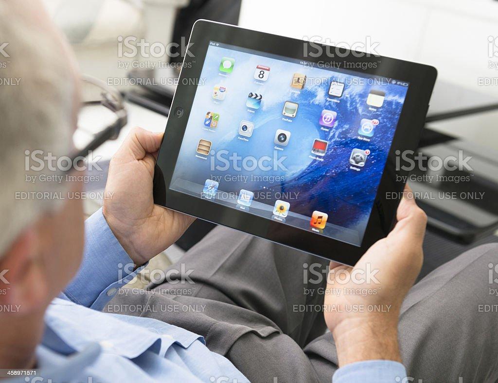 Senior man using an Ipad 3 on the living room royalty-free stock photo