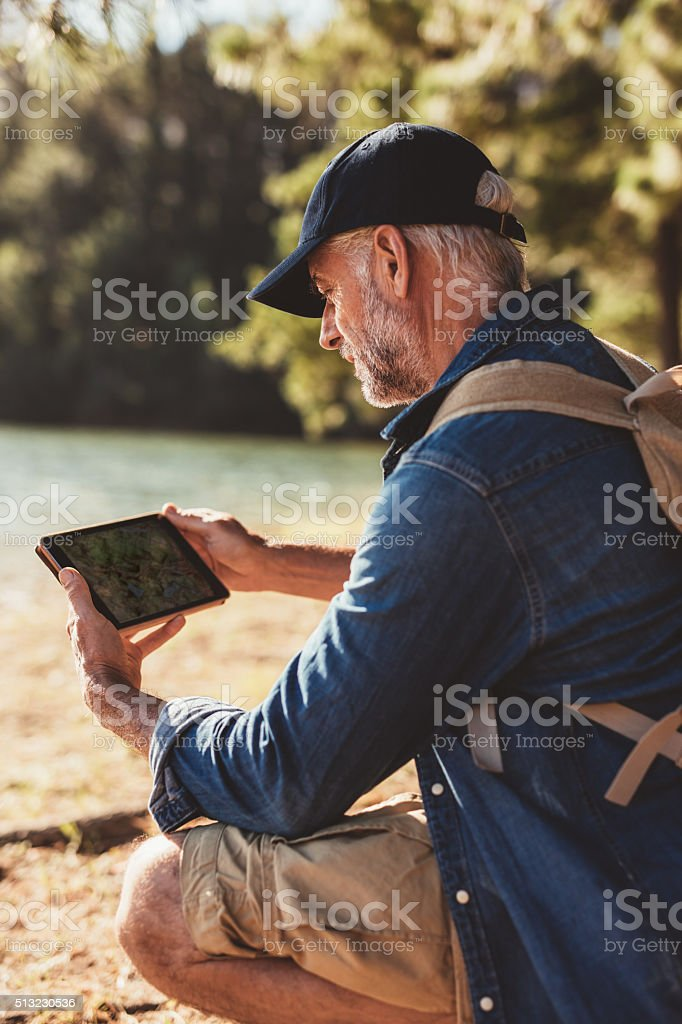 Senior man using digital tab in the forest for navigation stock photo