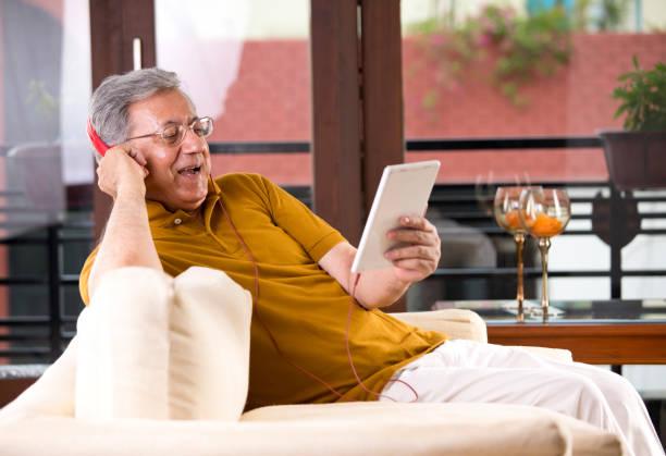 Senior-Mann mit digitalem Tablet und Kopfhörer – Foto