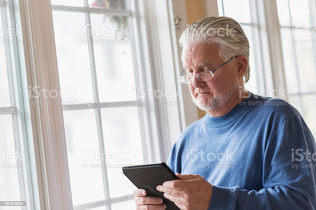 Senior man using digital tablet stock photo