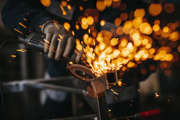 Senior man using electric grinder in workshop stock photo