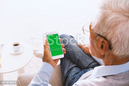 istock Senior man using green screen smartphone, sitting on couch 871816510