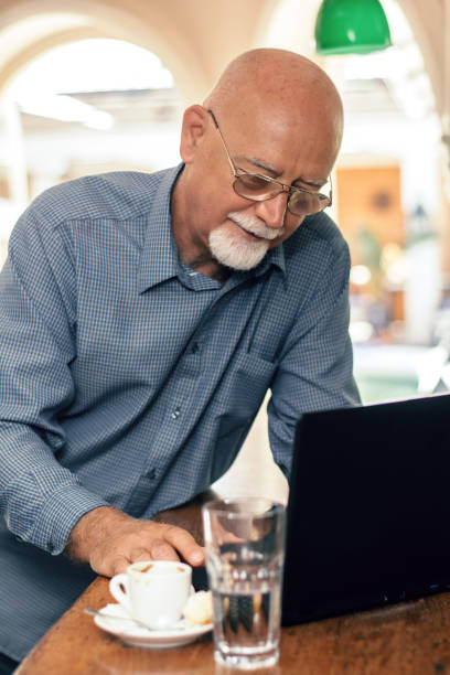 Senior man using laptop at bar counter Businessman in the cafe, using mobile phone and laptop old man working in a pub stock pictures, royalty-free photos & images