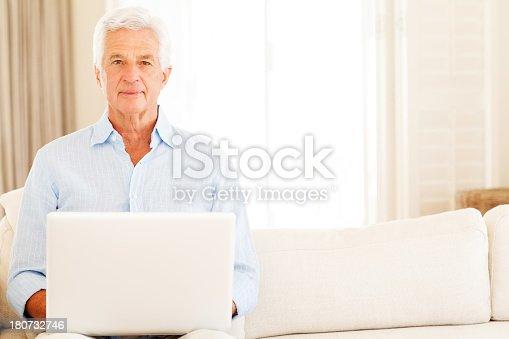 istock Senior Man Using Laptop On Sofa 180732746