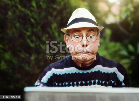 A senior man sitting in a garden using his laptop has a problem and glares at it, pulling a humorous face.