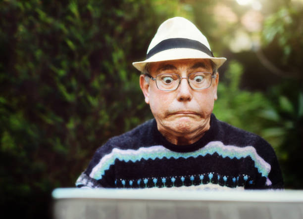 Senior man using laptop outdoors is confused and frustrated A senior man sitting in a garden using his laptop has a problem and glares at it, pulling a humorous face. mistake stock pictures, royalty-free photos & images