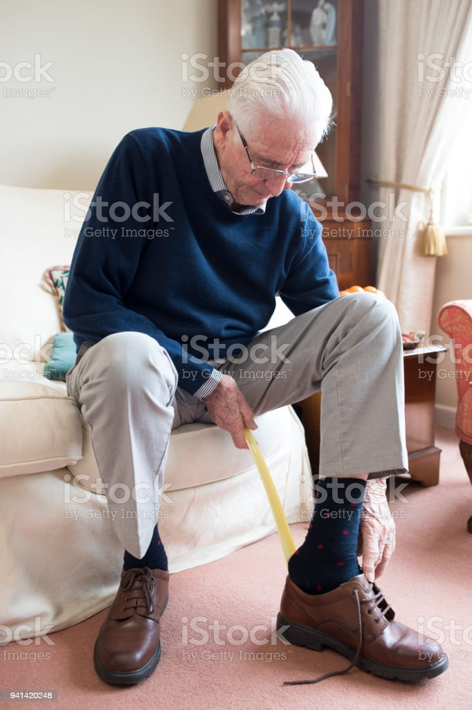 Senior woman mit langstieligen Schuhlöffel, Schuhe anziehen – Foto