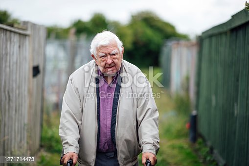 A shot of a senior man walking down a grass pathway between allotments. He is wearing casual clothing and is using a mobility walker.