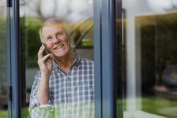 senior man using phone at window - old men window imagens e fotografias de stock