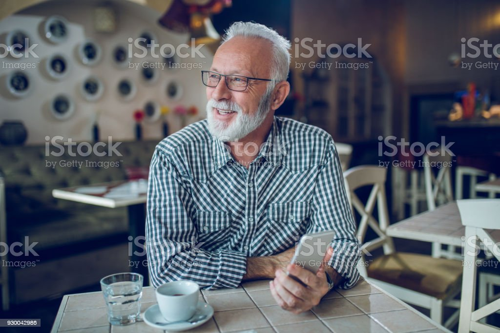 Senior man using smart phone in cafe stock photo