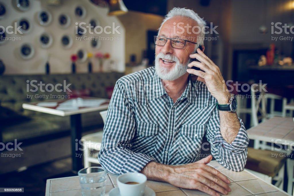 Senior man using smart phone in cafe stock photo