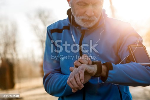 Elderly Man using Smart Watch measuring heart rate during walk