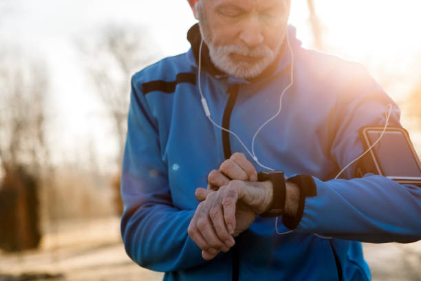 senior man using smart watch measuring heart rate - sports medicine stock photos and pictures