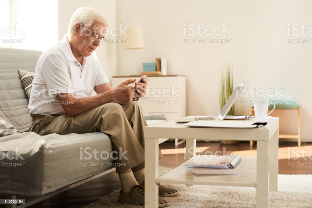 Senior hombre con Smartphone en casa - Foto de stock de 60-69 años libre de derechos