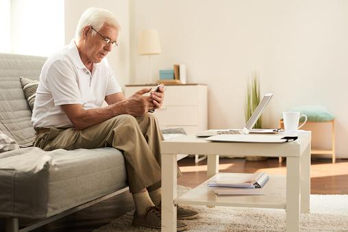Senior Hombre Con Smartphone En Casa Foto de stock y más banco de imágenes de 60-69 años