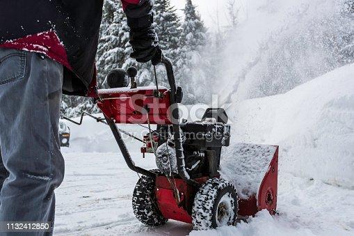 Senior Man Using SnowBlower After a Snowstorm, Quebec, Canada